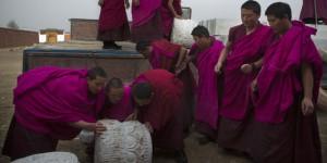 Des moines déchargent des matériaux de construction pour leur monastère.